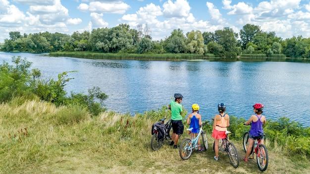 Семья на велосипедах на открытом воздухе, активные родители и дети на велосипедах, вид с воздуха на счастливую семью