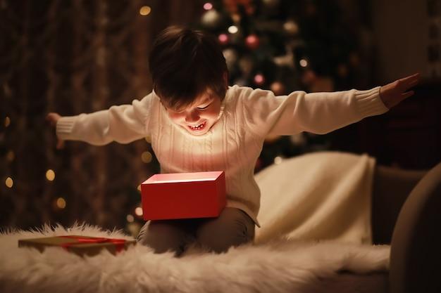 벽난로에서 크리스마스 이브에 가족입니다. 크리스마스 선물을 여는 아이들. 선물 상자가 있는 크리스마스 트리 아래 아이들. 전통적인 벽난로가 있는 장식된 거실. 집에서 아늑하고 따뜻한 겨울 저녁.