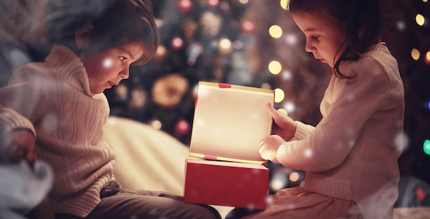 暖炉のクリスマスイブの家族。クリスマスプレゼントを開く子供たち。ギフトボックスとクリスマスツリーの下の子供たち。伝統的な暖炉のある装飾されたリビングルーム。自宅で居心地の良い暖かい冬の夜。