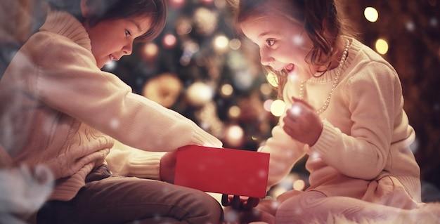 Семья в канун рождества у камина. дети открывают рождественские подарки. дети под елкой с подарочными коробками. украшенная гостиная с традиционным камином. уютный теплый зимний вечер дома.