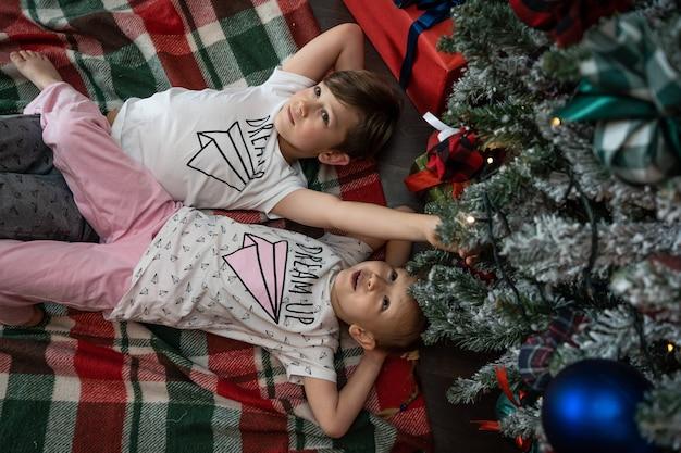クリスマスイブの家族。ギフトボックス付きのクリスマスツリーの下の子供たち。伝統的な暖炉のある装飾されたリビングルーム。居心地の良い暖かい冬の夜の家。