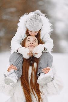家族のクリスマス休暇中の家族。公園の女性と少女。人々は歩きます。