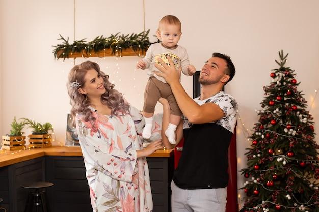 素敵な装飾が施されたクリスマスツリーの近くのキッチンにいる家族が、クリスマスの魔法を楽しんでいます。
