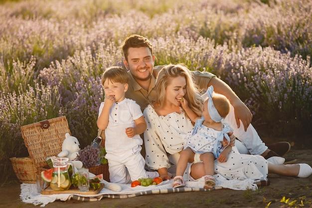 Семья на поле лаванды. люди на пикнике. мать с детьми ест фрукты.