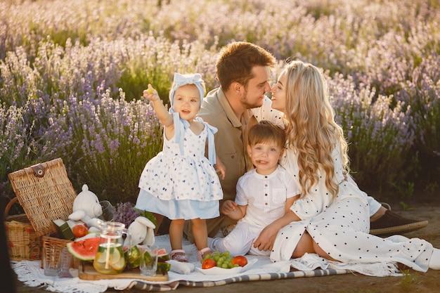 ラベンダー畑の家族。ピクニックの人々。子供を持つ母は果物を食べる。