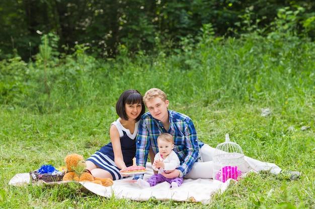 晴れた日にピクニックに家族。ピクニックや公園で遊んで幸せな混血家族。