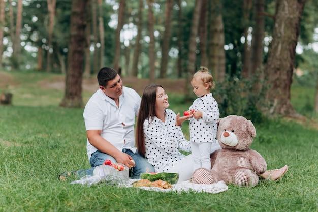 피크닉에 가족. 엄마, 아빠와 딸 공원에서 담요에 앉아. 여름 휴가의 개념. 어머니, 아버지, 아기의 날. 함께 시간을 보내십시오. 가족 모양