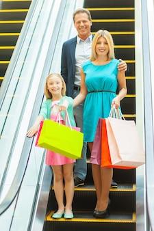 買い物をしている家族。ショッピングバッグを持ってエスカレーターで移動しながらカメラに微笑んで陽気な家族