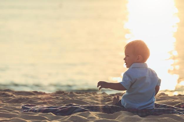 ビーチのコンセプト、日没の時間に熱帯のビーチで砂を保持している白人の男の子の家族