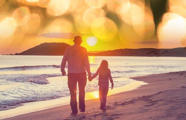 日没のビーチで家族。一緒に走っている母と娘。