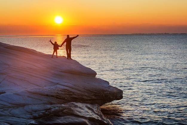Семья на пляже на закате. мать и дочь работают вместе.