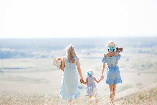 牧草地の家族。屋外の幸せな家族。家族は美しい風景に感心します。