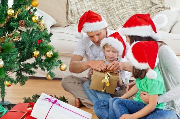 Семья открытия рождественские подарки, сидя на полу