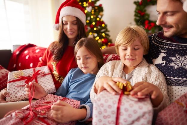 家でクリスマスプレゼントを開く家族