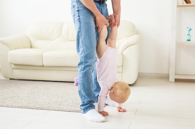 家族、親子関係、父性の概念-家で小さな女の赤ちゃんと遊ぶ幸せな父