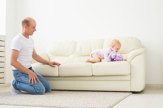 Концепция семьи, отцовства и отцовства - счастливый отец играет с маленькой девочкой дома