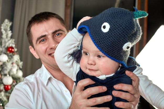家族、親子関係、人々の概念-家で小さな男の子と遊ぶ幸せな父