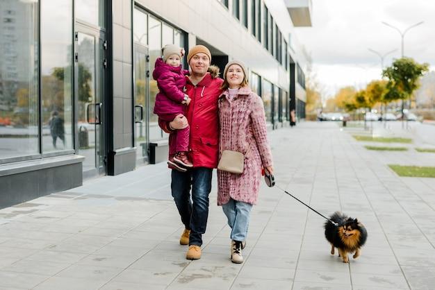 Семья, отцовство и люди концептуально-счастливая мать, отец и маленькая девочка гуляют в осеннем городе и веселятся.