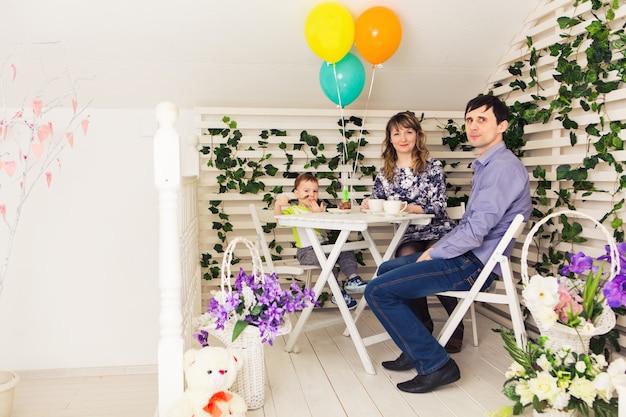 Семья, отцовство, с днем рождения и праздник концепции - счастливые родители и ребенок за столом, пьющим чай и едят торт.