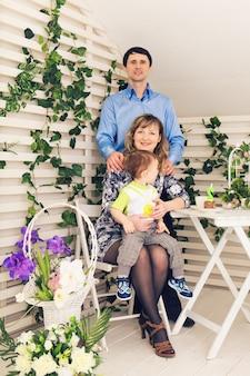 Семья, отцовство, с днем рождения и концепция праздника - портрет счастливых родителей и ребенка за столом, пьющим чай и едящим торт.
