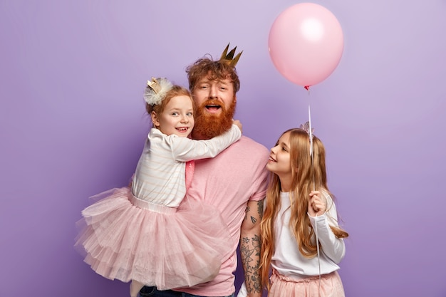 Family, parenthood and holidays concept. funny father entertains children, carries small daughter on hands, decorate room before party, wear festive clothes, isolated over purple wall.