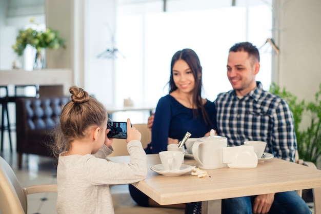 Family, parenthood, technology people concept. close up of happy mother, father and little girl having dinner, kid taking photo by smartphone at restaurant