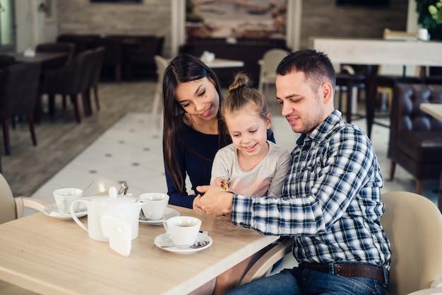 가족, 부모, 기술 사람들 개념. 행복 한 어머니, 아버지와 어린 소녀 저녁 식사 레스토랑에서 스마트 폰으로 셀카를 복용