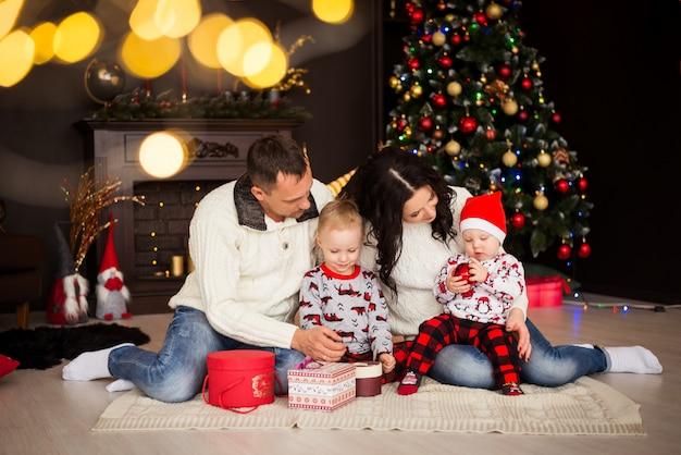 家族。クリスマスコスチュームの親と子供、クリスマスデコレーション付きのパジャマ