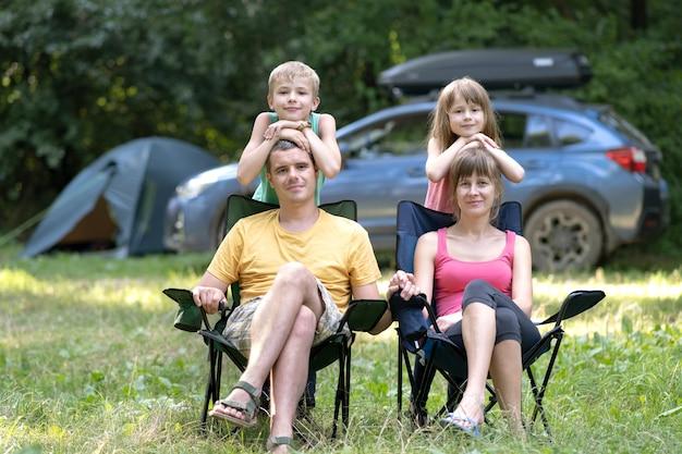 여름에 캠핑 장에서 함께 쉬고있는 가족 부모와 아이들