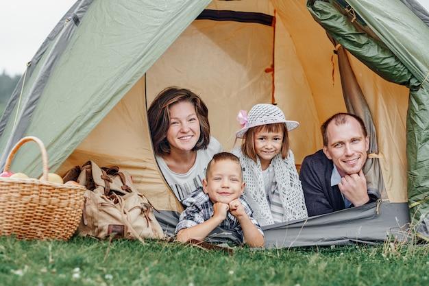 캠프 텐트에서 가족 부모와 두 자녀. 여름 방학에 행복 한 어머니, 아버지, 아들과 딸