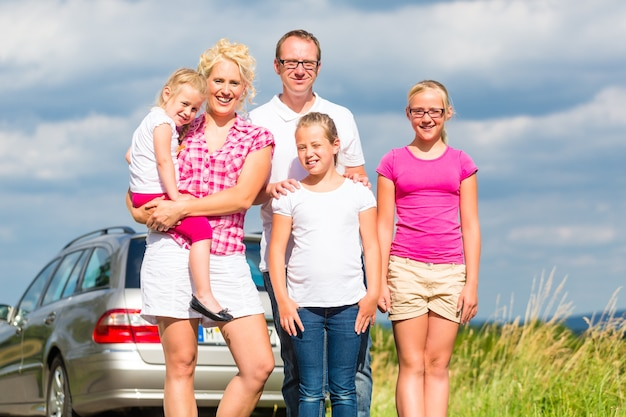 Family of parents and children standing in front of car in countryside
