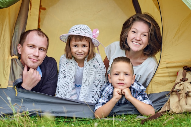 Family parents and two children in camp tent.