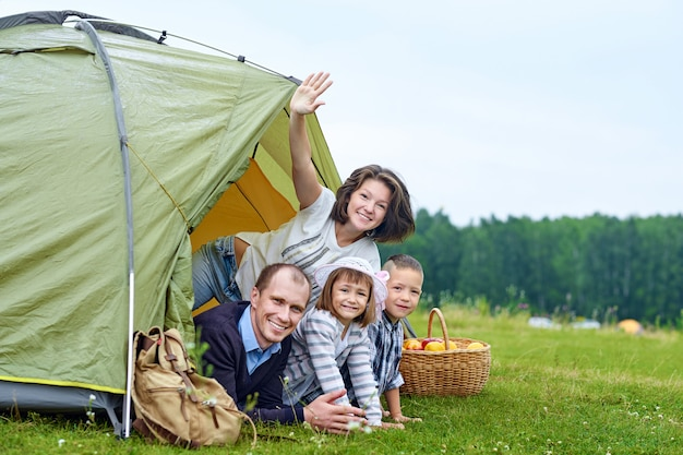 Family parents and two children in camp tent