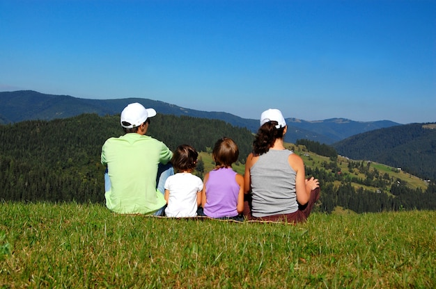 Family of parents and two kids sitting on the grass and looking at the beautiful mountain view