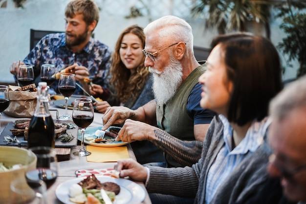 バーベキューディナーで食べる家族-屋外で食事を楽しむ多民族の友人-食べ物、友情、集まり、夏のライフスタイルのコンセプト-流行に敏感な男の顔に焦点を当てる