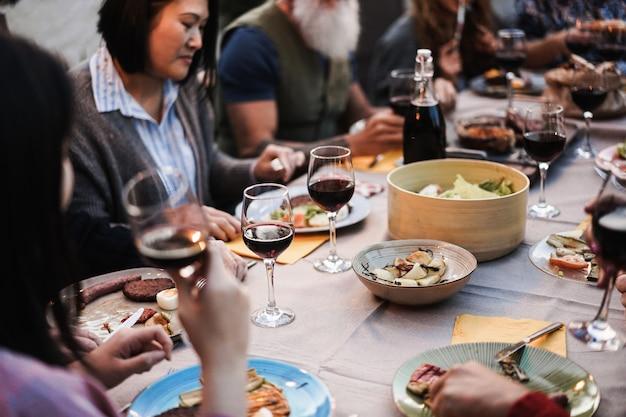 バーベキューディナーを楽しんでいる家族-屋外でバーベキュー料理を食べている多民族の友人-食べ物、友情、集まり、夏のライフスタイルのコンセプト-センターワイングラスに焦点を当てる
