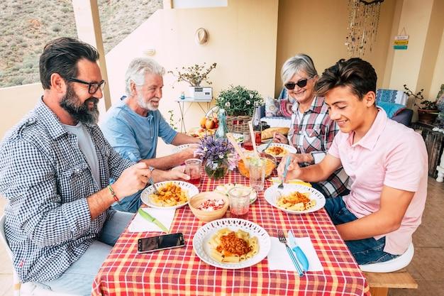 赤いテーブルで一緒に家族の人々の屋外ランチ