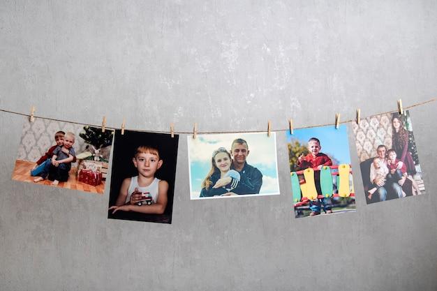 Открытки с семейными фотографиями висят на веревке. воспоминания. домашняя фотогалерея, оригинальная фотовыставка. лучшие моменты.