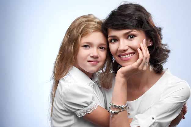 Family photo of a happy couple: smiling a mother and her beloved daughter. they are very pretty and nice. they were white t-shirts and hug each other.