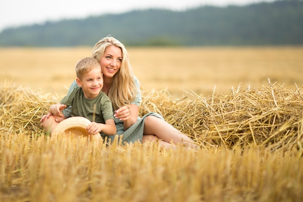 Family photo: mom blonde with long hair and son playing in the field