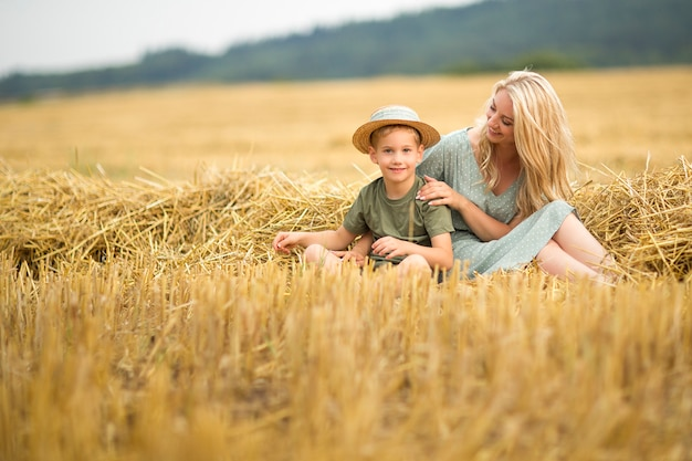 Family photo: mom blonde with long hair in a straw hat and son playing in the field