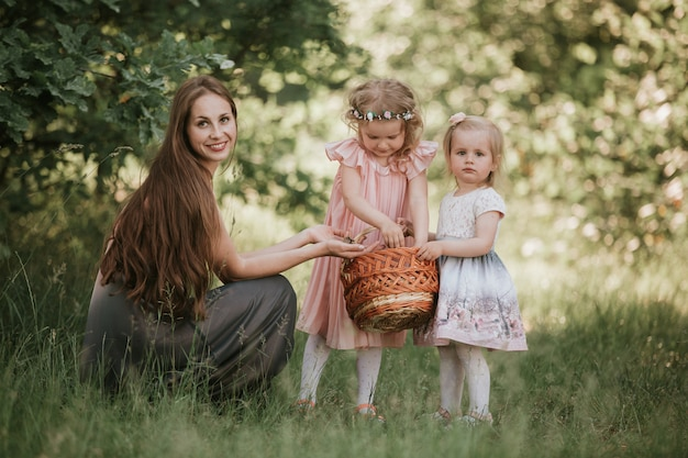 Family photo mom with daughters in the park. photo of young mother with two cute kids outdoors in spring time, beautiful woman with daughter having fun