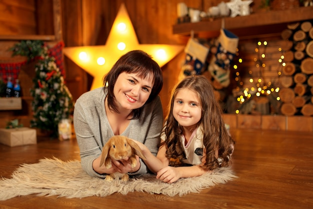 Family photo of mother and daughter laying on the floor at fireplace with cute rabbit. christmas decoration