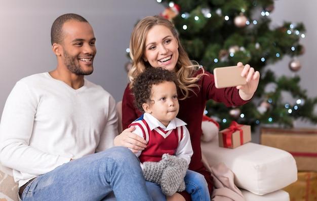 家族の写真。ソファに一緒に座って、写真のポーズをとっている間笑顔で素敵な幸せな若い家族