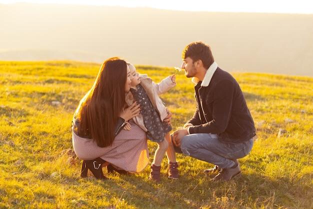 일몰에 자연에 딸과 함께 시간을 보내고 행복한 부모의 가족 사진