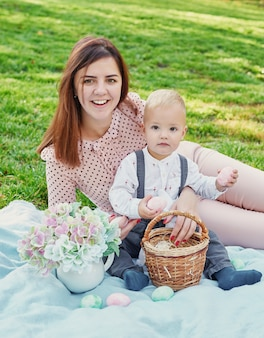 Family photo session of mom and baby son for easter in the park, next to them is a basket with eggs and an easter rabbit