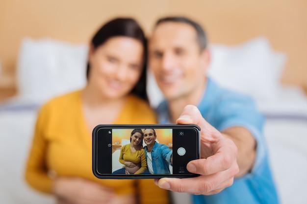 Семейное фото. силуэт счастливой пары, ожидающей ребенка, выражающей позитив и позирующей