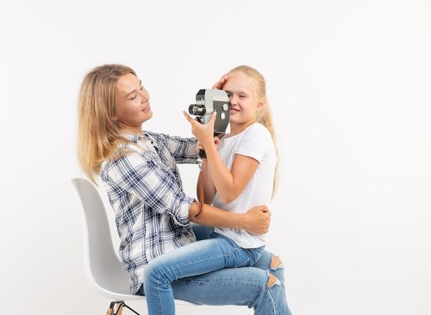 가족, 사진 및 취미 개념-여자와 흰색 배경에 구식 카메라를 사용하는 그녀의 아이.