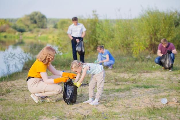 家族は夏にビーチでゴミを拾う