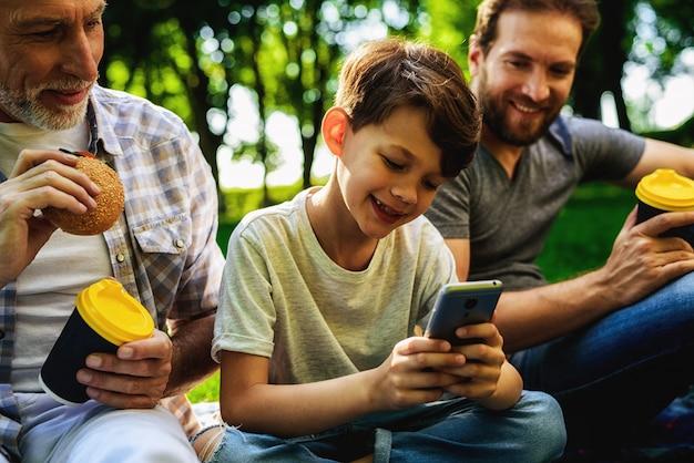 Family picnic. boy watch smartphone.